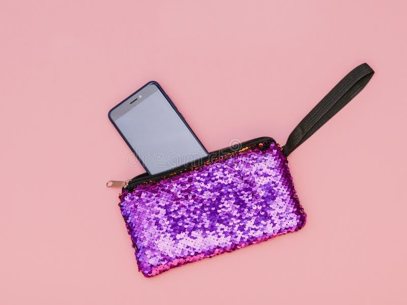 Telefon i błyszcząca purpurowa kobiety torebka na różowym tle Mieszkanie nieatutowy fotografia stock