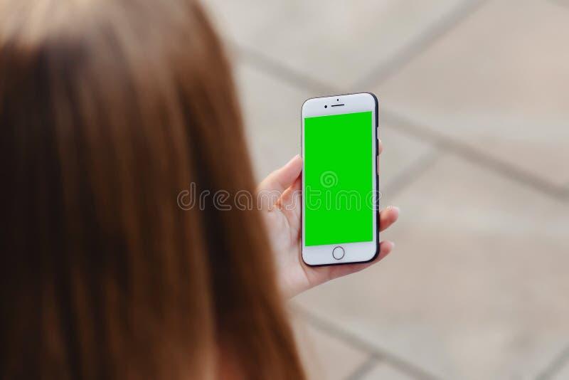 Telefon i exakta flickahänder med den gröna skärmen royaltyfri fotografi