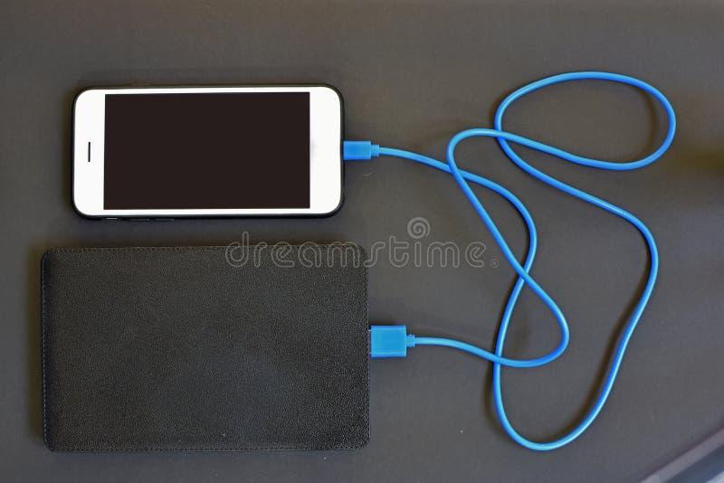 Telefon komórkowy ładuje z władza bankiem obraz stock