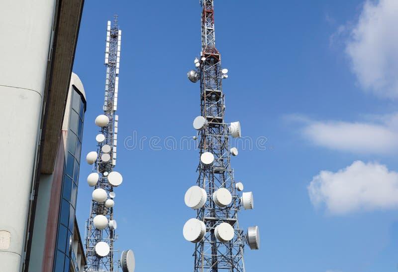 Telefon komórkowy anteny komunikacyjny wierza z anteną satelitarną na niebieskiego nieba tle, telekomunikaci wierza fotografia royalty free
