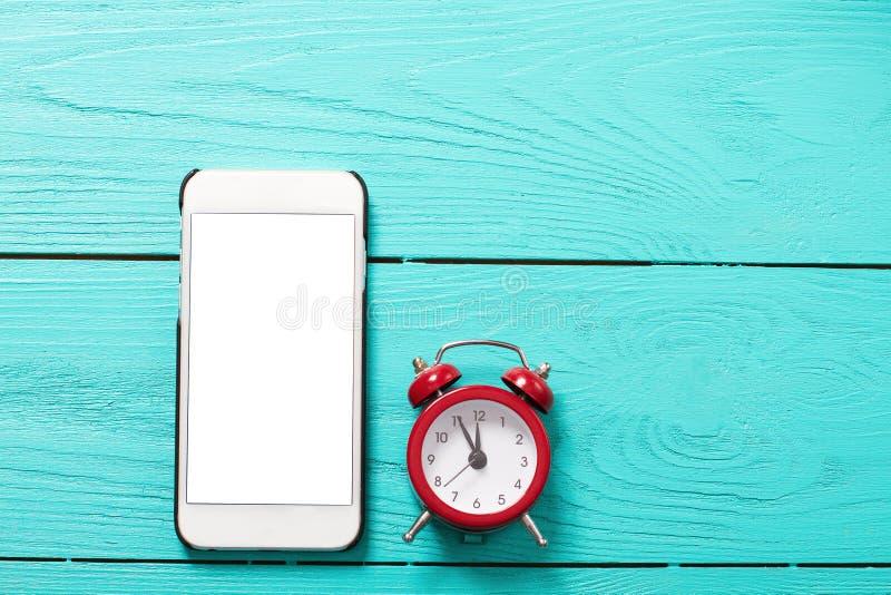 Telefon komórkowy, czerwony retro budzik z pięć minutami i dwanaście o ` zegar na błękitnym drewnianym tle Odgórny widok i pusty  obrazy royalty free