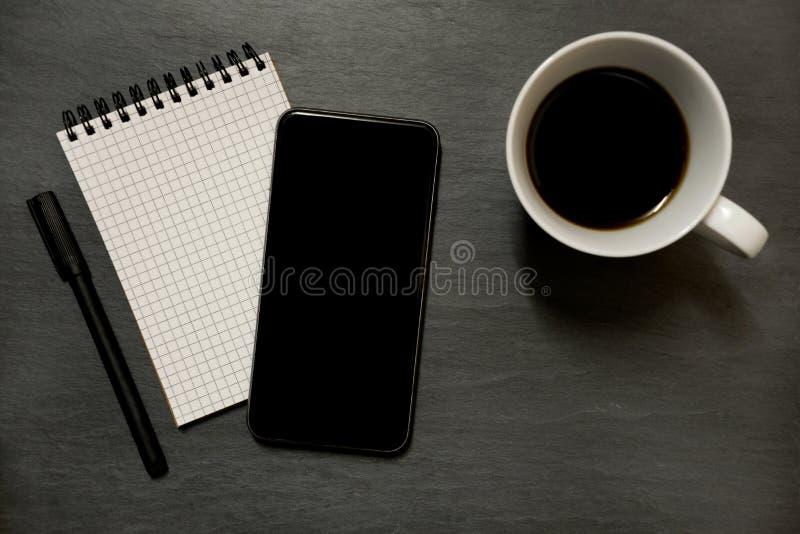 Telefon komórkowy, gridded notowany ochraniacz i filiżanka kawy, - na zmroku łupku zdjęcia royalty free