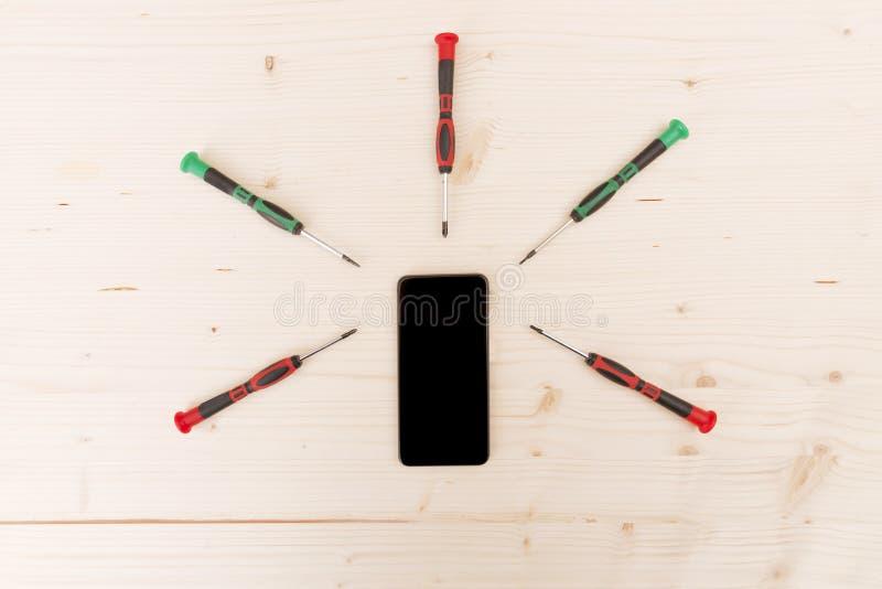 Telefon komórkowy naprawa Telefon z śrubokrętami wokoło na drewnianych półdupkach zdjęcia royalty free