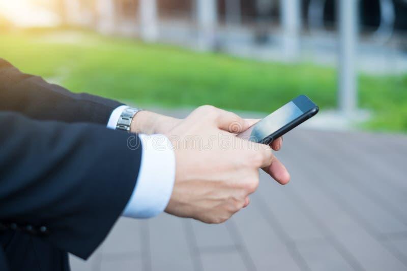 Telefon komórkowy w biznesmenie wręcza plenerowego obraz stock