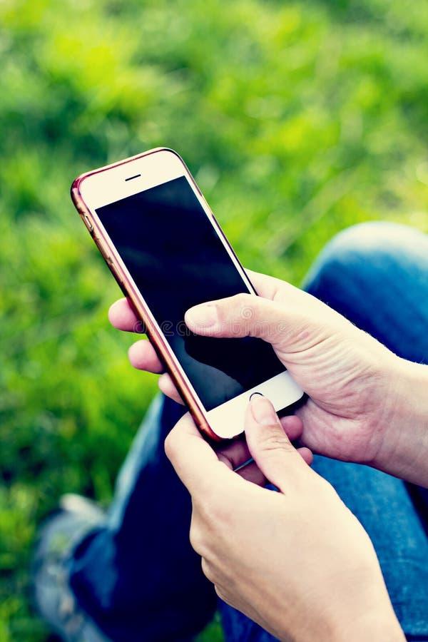 Telefon komórkowy w kobiety ręce w deckchair przeciw tłu rzeka Telefon, Deckchair, zielona trawa, rzeka Czas t zdjęcie royalty free