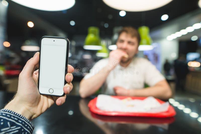 Telefon komórkowy z białym ekranem z tyłu mężczyzna który je fast food przy restauracją Fast food dla lunchu fotografia stock