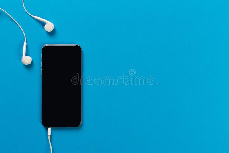 Telefon komórkowy z białymi słuchawkami na colour backgroung, odgórny widok zdjęcia royalty free