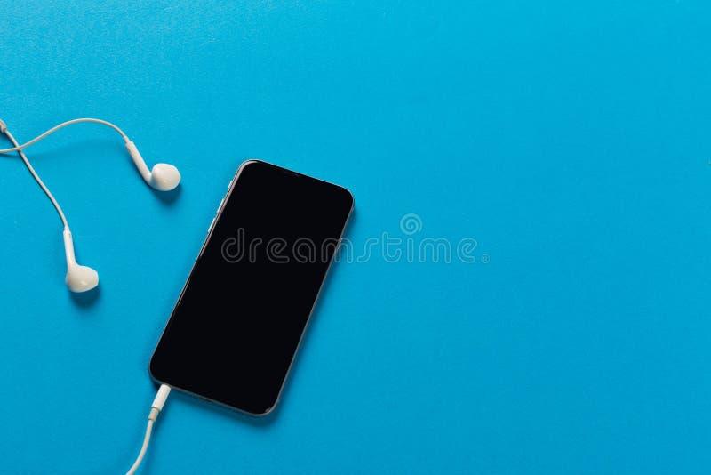 Telefon komórkowy z białymi słuchawkami na colour backgroung, odgórny widok obraz stock
