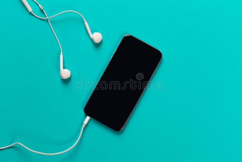Telefon komórkowy z białymi słuchawkami na colour backgroung, odgórny widok zdjęcia stock