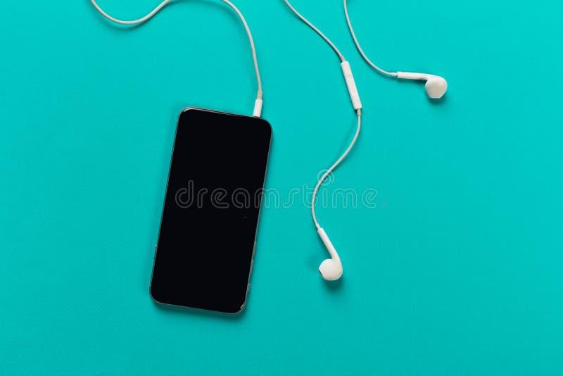 Telefon komórkowy z białymi słuchawkami na colour backgroung, odgórny widok obraz royalty free