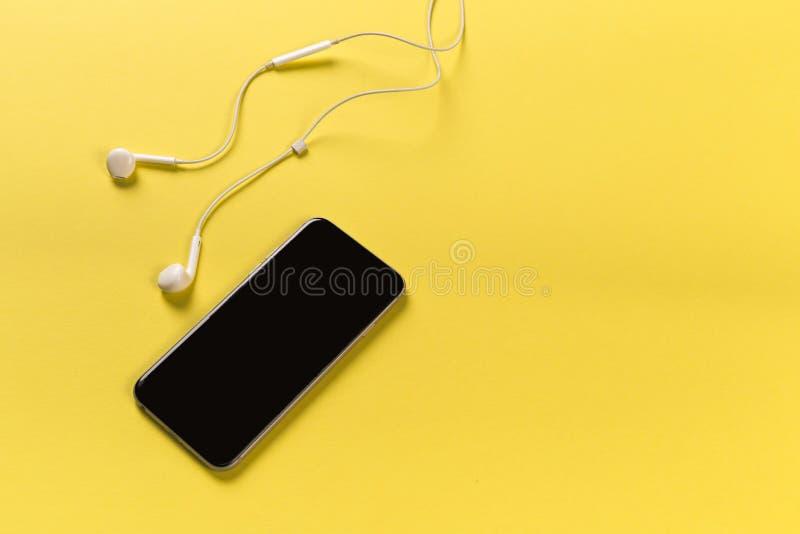 Telefon komórkowy z białymi słuchawkami na colour backgroung, odgórny widok fotografia stock