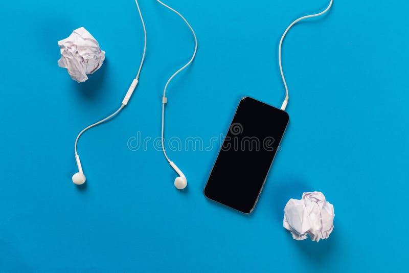 Telefon komórkowy z białymi słuchawkami na colour backgroung z rolką zdjęcia royalty free