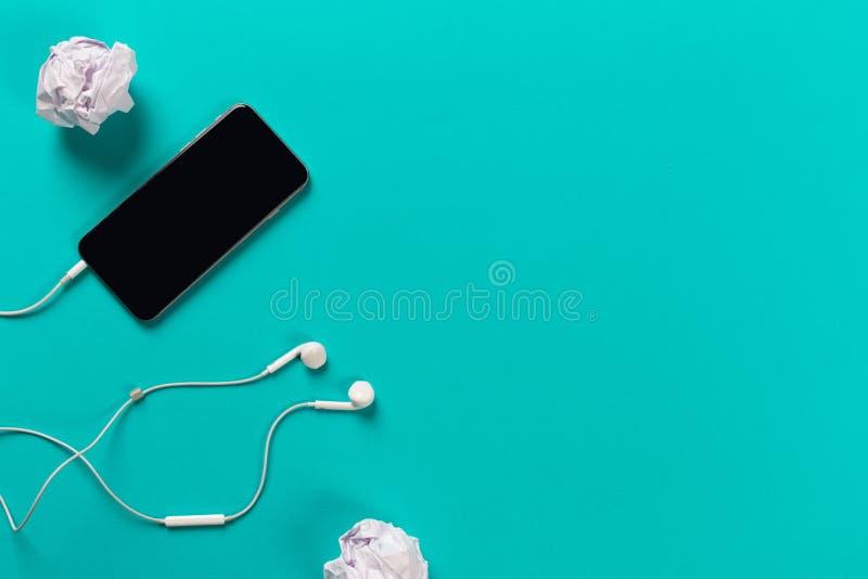 Telefon komórkowy z białymi słuchawkami na colour backgroung z staczającym się papierem, odgórny widok zdjęcia stock