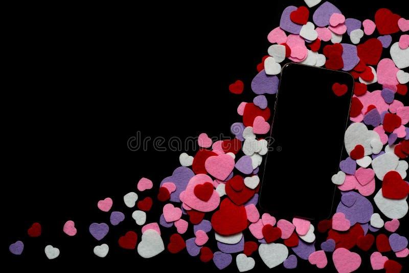 Telefon komórkowy z coloured odczuwanymi sercami na gorących menchii tle - texting, gawędzi, valentines, miłość fotografia royalty free