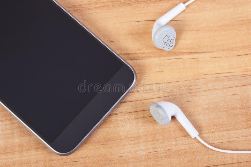 Telefon komórkowy z hełmofonami, używać elektroniki wyposażenie obraz stock