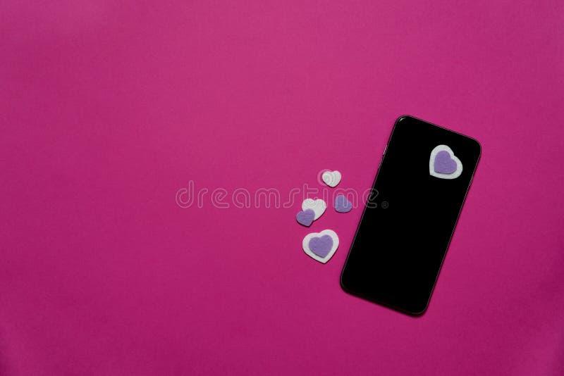 Telefon komórkowy z purpurowymi i białymi odczuwanymi sercami na gorących menchii tle - texting, gawędzi, valentines, miłość zdjęcia stock