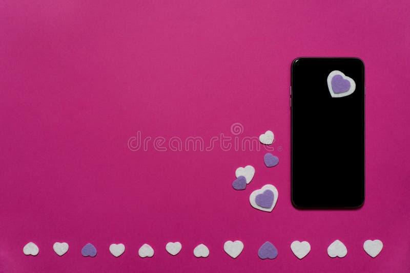 Telefon komórkowy z purpurowymi i białymi odczuwanymi sercami na gorących menchii tle - texting, gawędzi, valentines, miłość zdjęcie stock