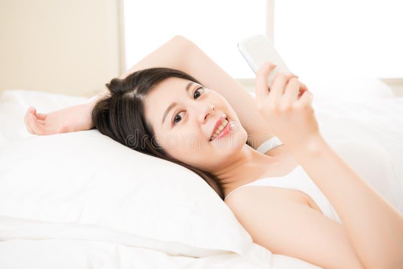 Telefon-Lesetextnachricht des entspannten asiatischen Frauengebrauches intelligente stockbild