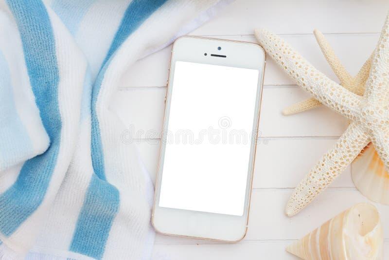 Telefon med strandhandduken och snäckskal royaltyfri bild