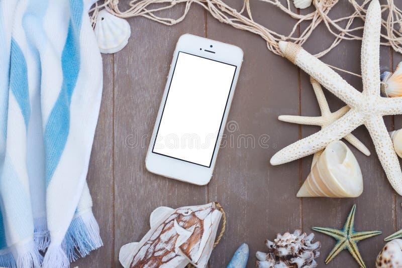 Telefon med strandhandduken och snäckskal arkivbild