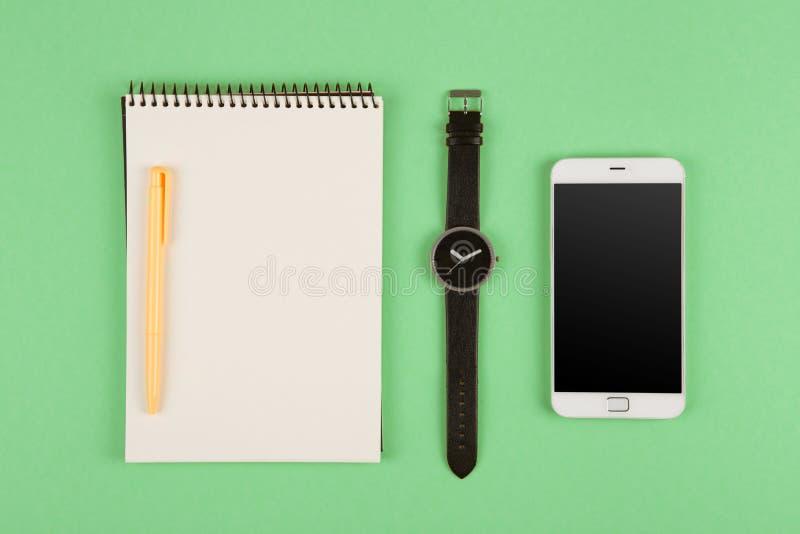 Telefon, notepad, klocka och penna på färgbakgrunden royaltyfri bild
