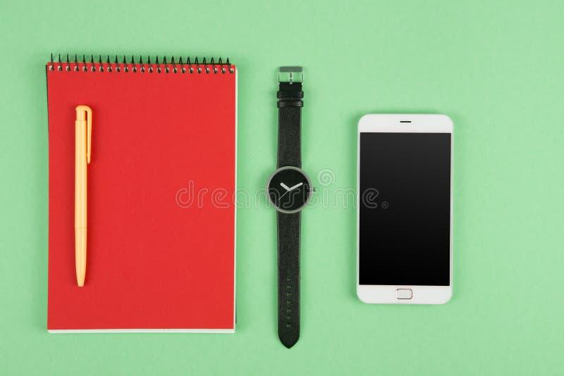Telefon, notepad, klocka och penna på färgbakgrunden arkivfoton