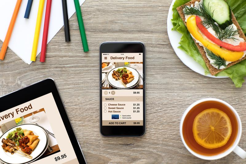 Telefon- och datorminnestavla med app-leveransmat på skärmen royaltyfri fotografi