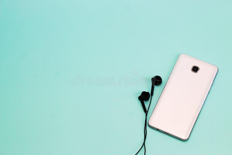 Telefon och hörlurar på en ljus bakgrund Bakgrund med utrymme f?r text royaltyfri fotografi