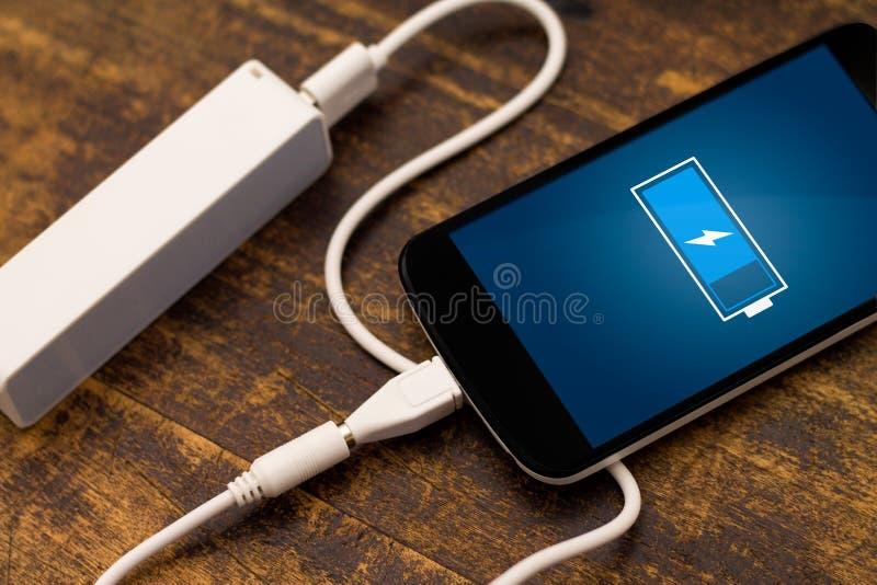 Telefon som laddar med energibanken. royaltyfri fotografi