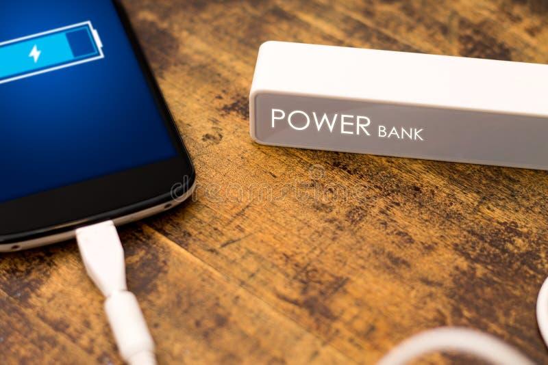 Telefon som laddar med energibanken. royaltyfria bilder