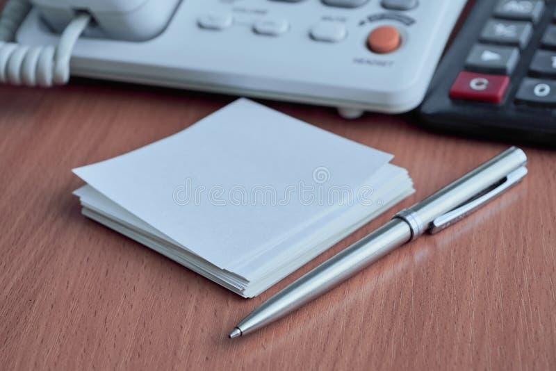 Telefon, Taschenrechner, Weißbuch für Anmerkungen und Metallkugelschreiber stockbild