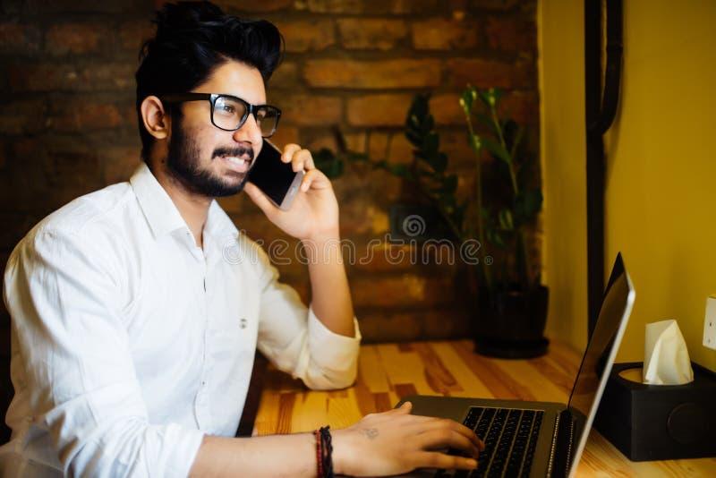 Telefon till kollegan Säker ung man i smarta tillfälliga kläder som rymmer den smarta telefonen och ser yttersidan, medan sitta p fotografering för bildbyråer