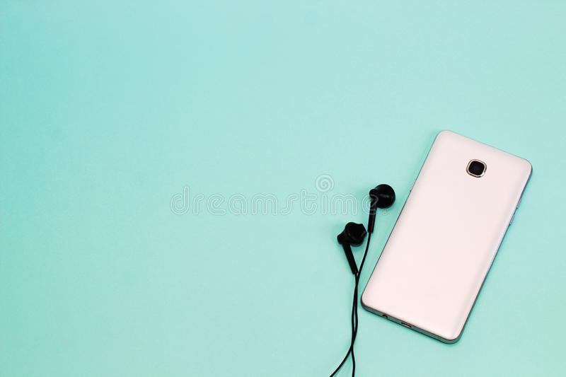 Telefon und Kopfhörer auf einem hellen Hintergrund Hintergrund mit Raum f?r Text lizenzfreie stockfotografie