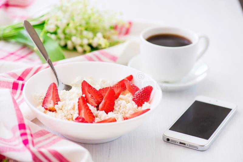 Telefon und Tasse Kaffee mit Platte des Hüttenkäses mit strawb lizenzfreie stockfotografie
