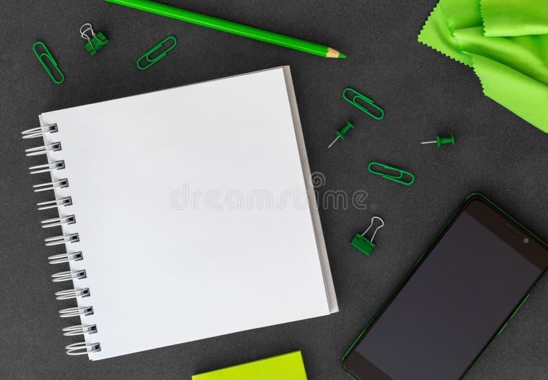 Telefon z pustym biel spirali papieru notatnikiem, barwionym ołówkiem, papierowymi klamerkami, papierowymi kępami i zielonym p fotografia royalty free