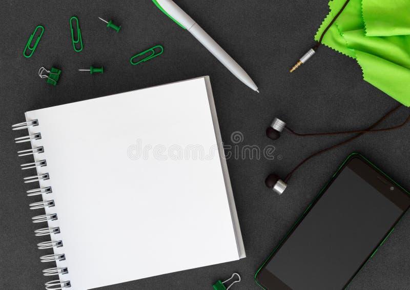 Telefon z pustym biel spirali papieru notatnikiem, piórem, papierowymi klamerkami, papierowymi kępami, hełmofonami i zielonym  zdjęcia stock