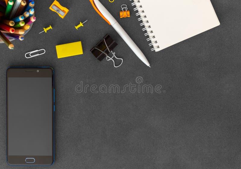 Telefon z pustym biel spirali papieru notatnikiem, pióro, papierowe kępy, papierowe klamerki, gumka, ostrzarka na ciemnym tle zdjęcie stock