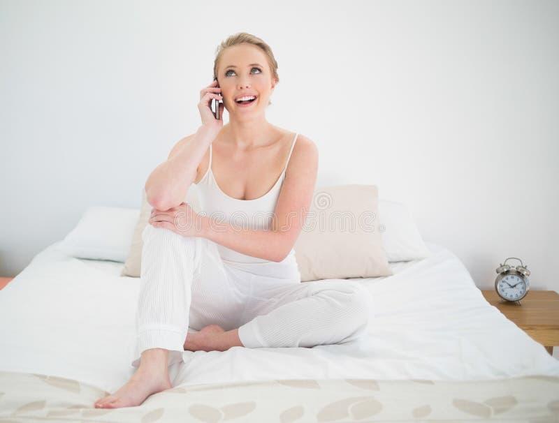 Telefonar louro alegre natural ao sentar-se na cama fotos de stock royalty free