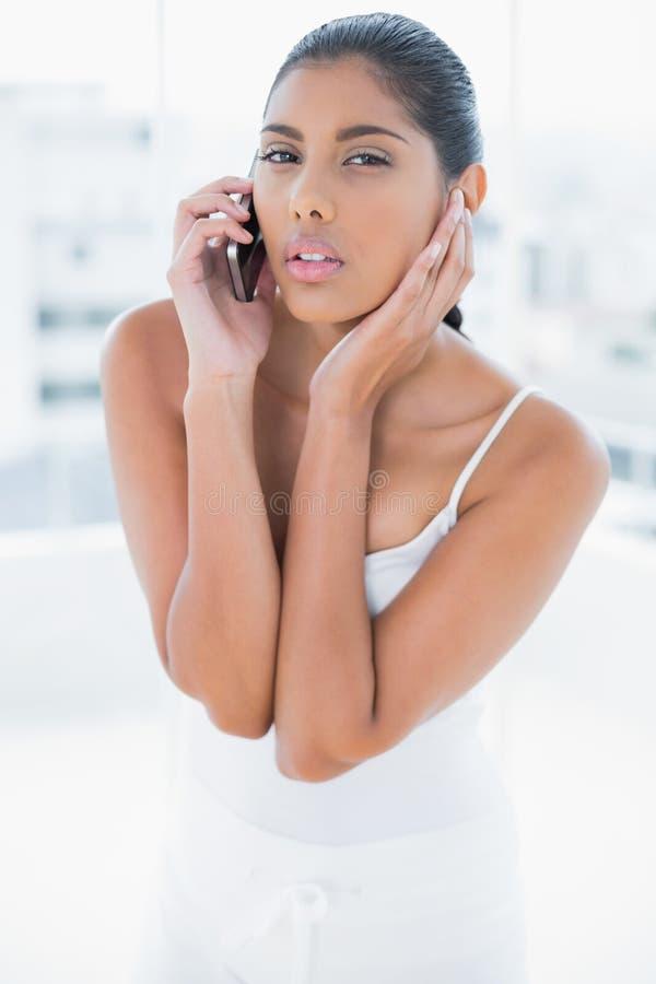 Telefonata castana tonificata aggrottante le sopracciglia con il telefono cellulare immagini stock