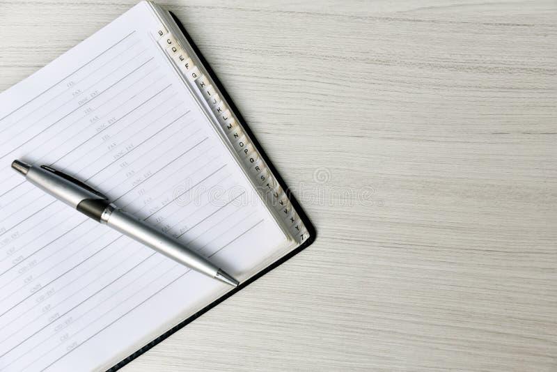 Telefonbuch mit Stift auf weißer Tabelle lizenzfreie stockfotos