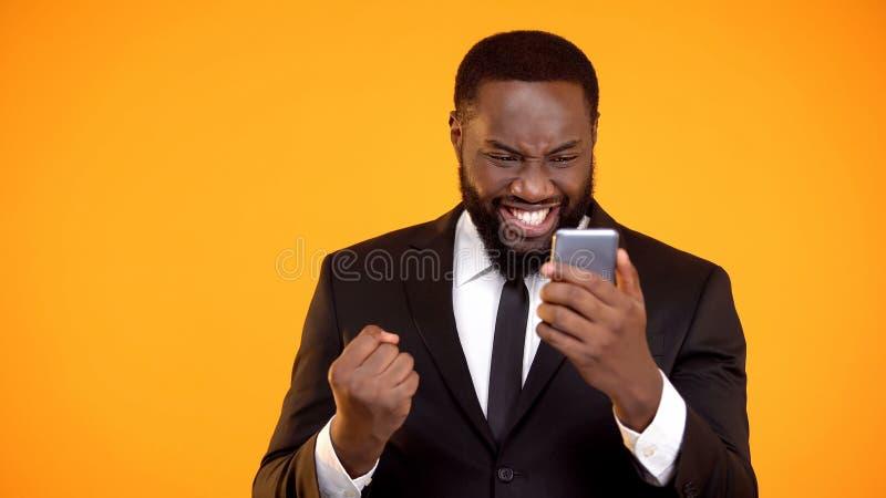 Telefone afro-americano extremamente feliz da terra arrendada do homem e fatura sim do gesto, vit?ria imagens de stock royalty free