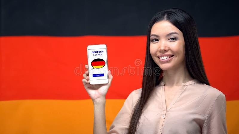 Telefone agradável da terra arrendada da mulher com o app do estudo da língua, bandeira alemão no fundo fotos de stock