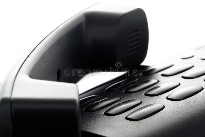 Telefone ajustado sobre o teclado imagem de stock