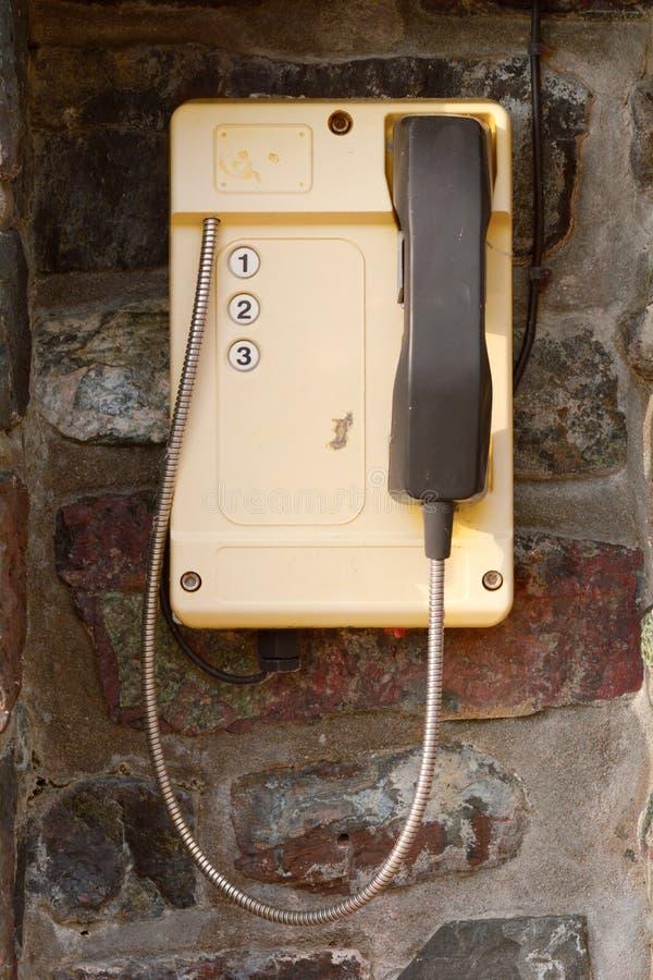 Telefone amarelo com os três números para chamar a guarda costeira fotografia de stock