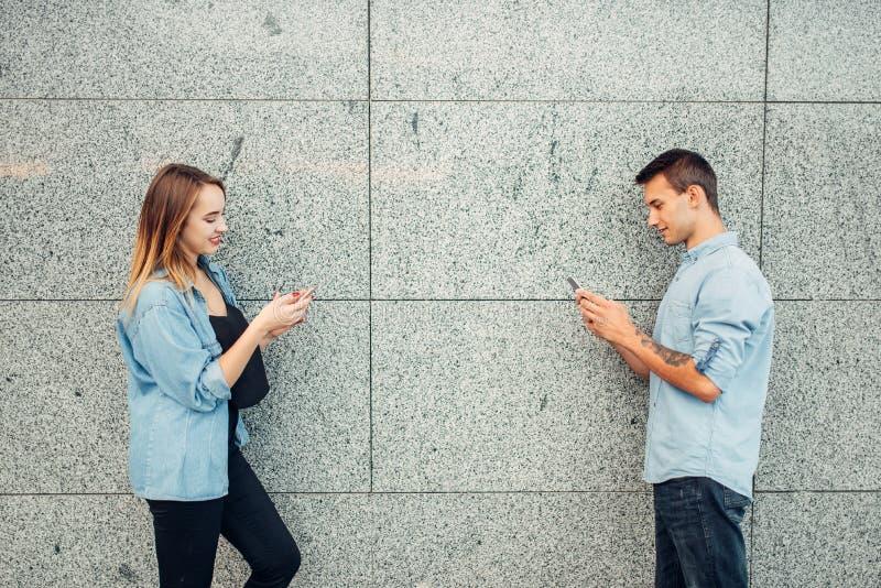 Telefone ao homem do viciado e à mulher, problema do apego fotografia de stock
