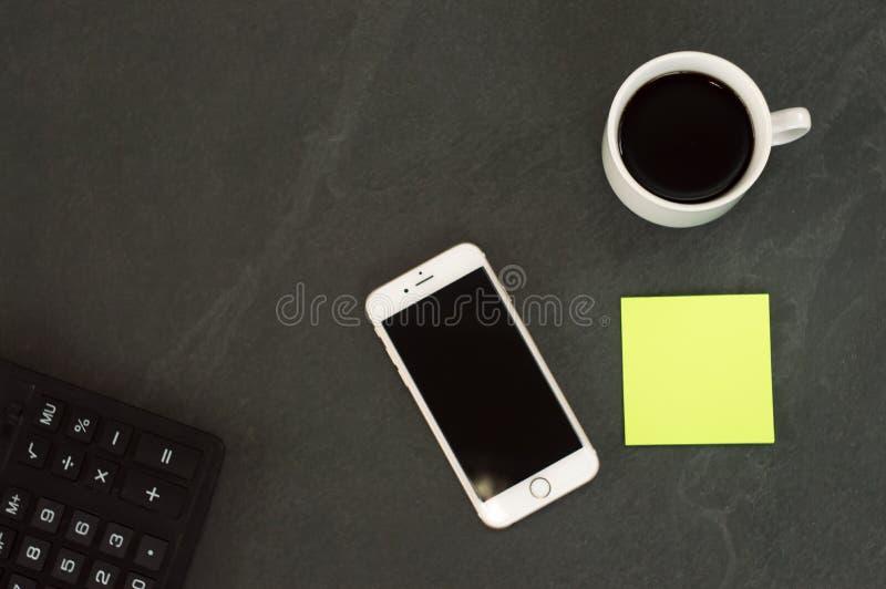 Telefone branco com uma x?cara de caf?, uma pena vermelha e uma mentira da calculadora em uma tabela de madeira branca foto de stock