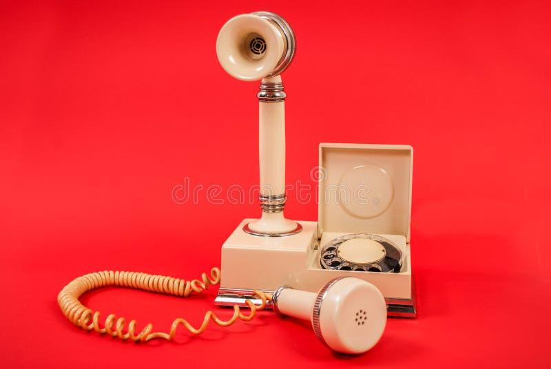 Telefone branco muito velho isolado em um fundo vermelho foto de stock