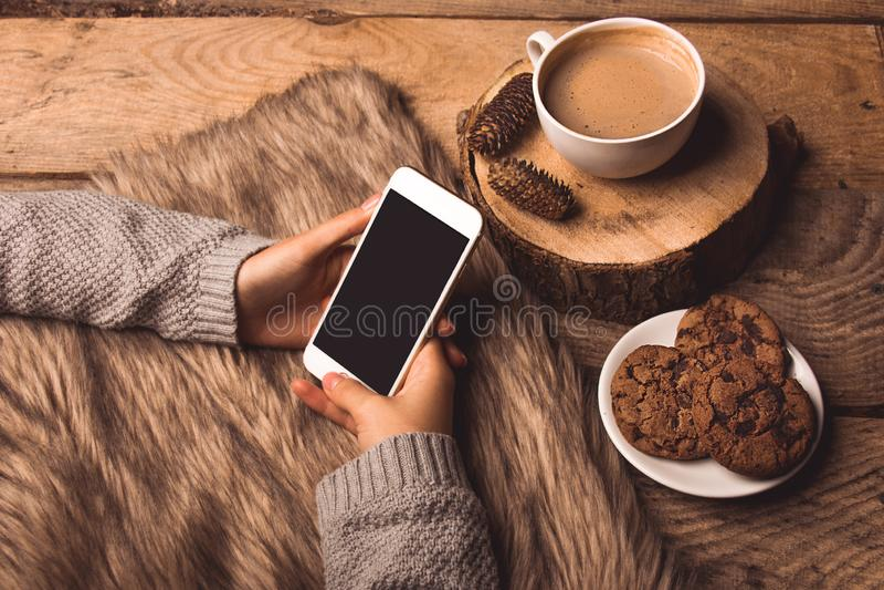 Telefone branco nas mãos da menina, das cookies do café, dos cones e da pele imagem de stock royalty free