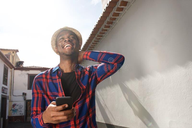 Telefone celular afro-americano feliz da terra arrendada do homem fora fotografia de stock