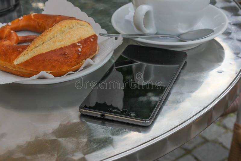 telefone celular ao lado de um cappuccino italiano fotos de stock royalty free